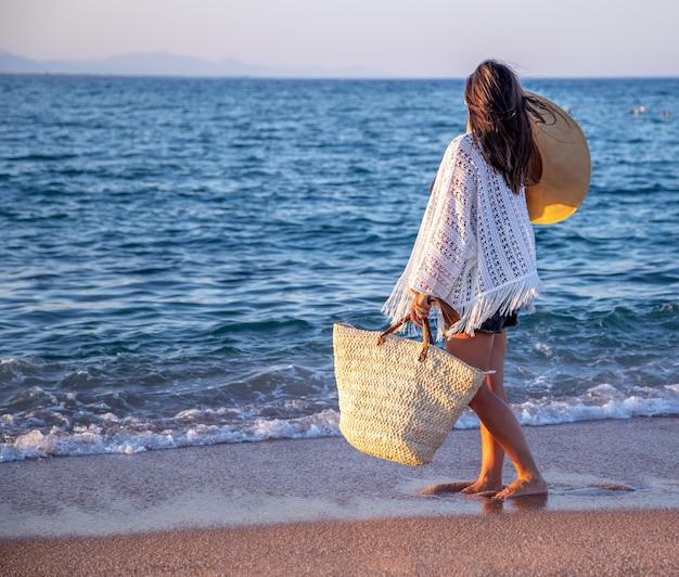手に帽子と籐のバッグを持った少女が海岸を歩いています。夏休みのコンセプト。