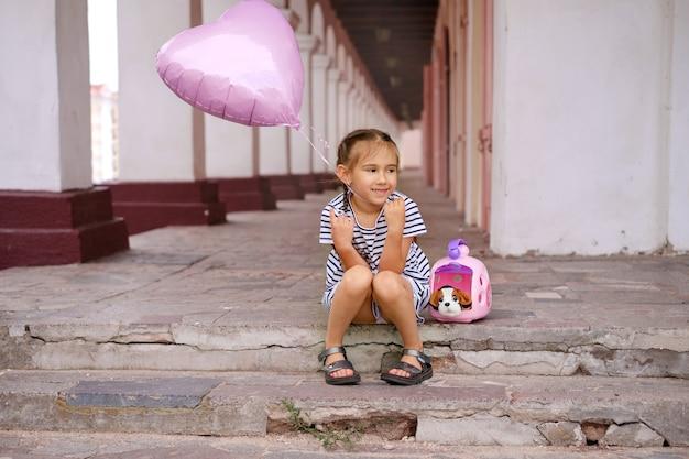 ハート型の風船を持った女の子がおもちゃの犬と一緒に街の階段に座っています