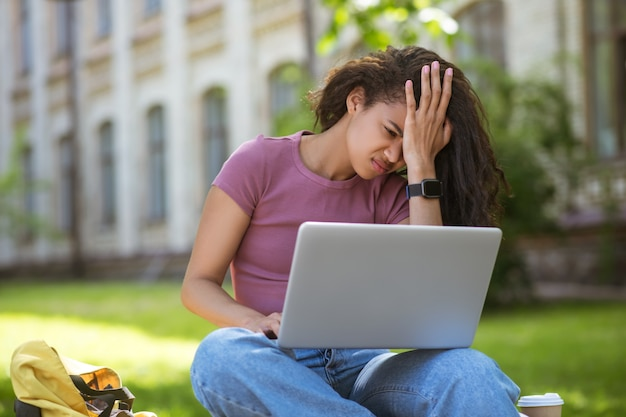 Девушка с ноутбуком сидит на траве и выглядит уставшей