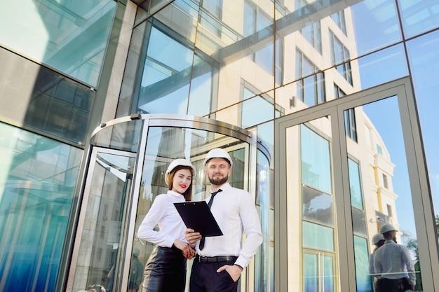 그림 흰색 건설 헬멧과 흰색 셔츠에 남자와 여자