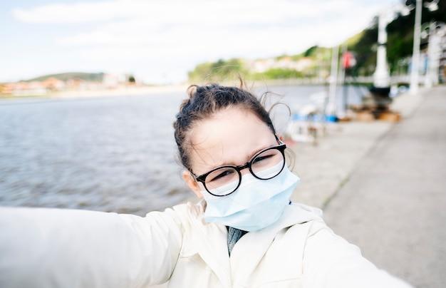 Девушка с маской в рыбацком порту в городе, принимая селфи