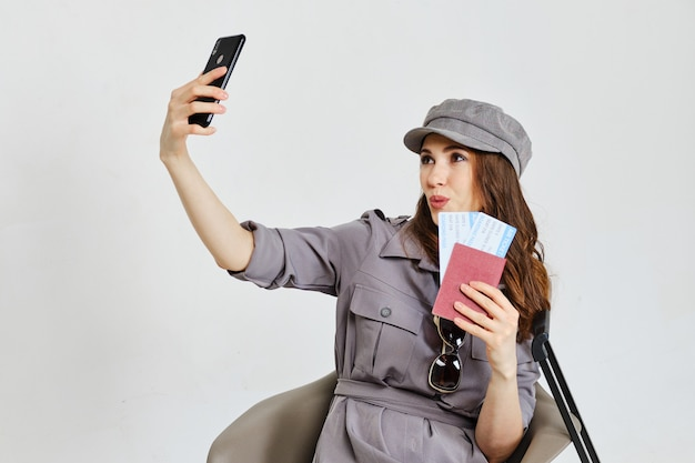 Девушка с паспортом, билеты делает селфи фото на смартфон.