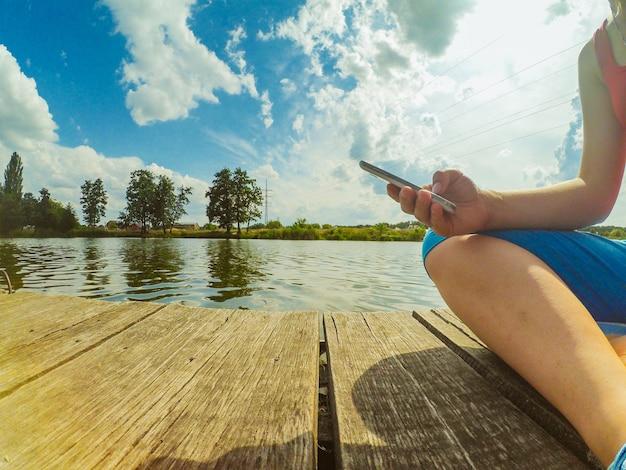 손에 전화기를 들고 있는 소녀가 수면 근처의 나무 표면에 앉아 있습니다. 아래에서 쐈어. 광각 액션캠 고프로.