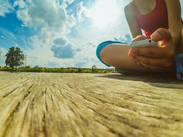 그녀의 손에 전화를 가진 소녀는 나무 표면에 앉아