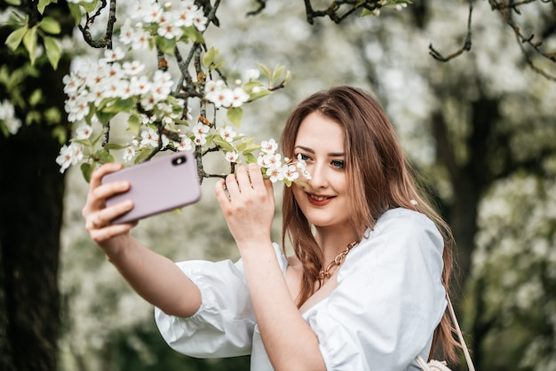 Девушка с телефоном в руке фотографирует селфи, фото для интернета
