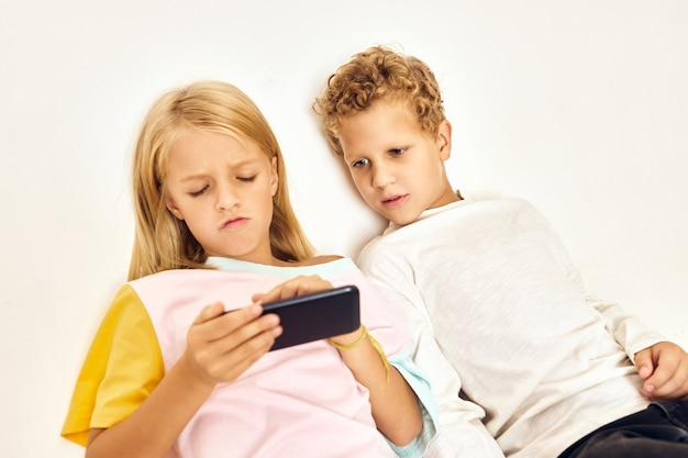 ゲームをしている男の子の隣に携帯電話を持っている女の子。高品質の写真