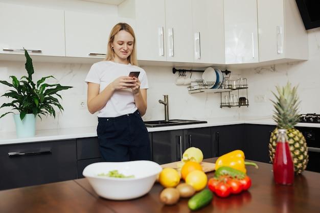 전화를 든 소녀가 부엌에 서서 건강에 좋은 음식을 요리하기위한 새로운 조리법을 찾습니다.