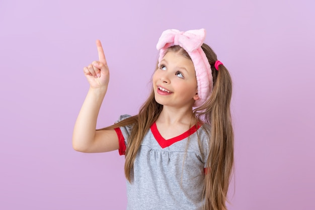 머리에 분홍색 활을 쓴 소녀가 위를 가리키고 있습니다.