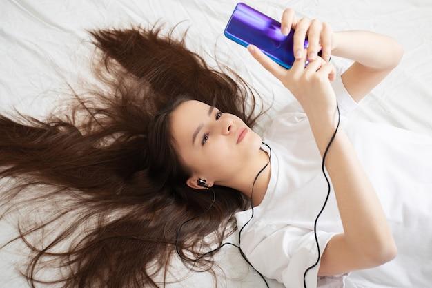 ベッドにスマートフォンを持った女の子が自撮りしながら音楽を聴いている