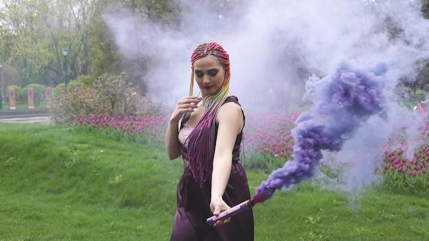 Девушка с улыбкой с ярким макияжем и разноцветными косами