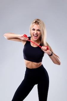 Девушка со спортивной фигурой выполняет упражнения с резинкой для фитнеса