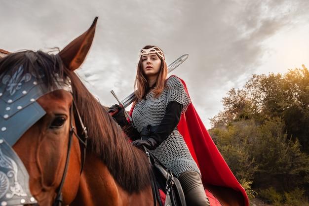 空を背景に馬に剣を持った少女。戦士の衣装を着た美しい女性