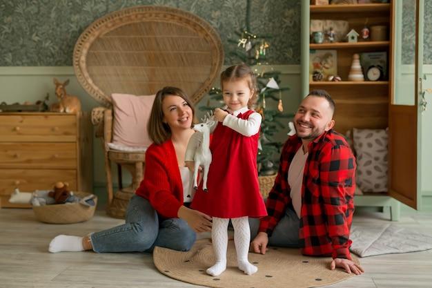 おもちゃの鹿を手にした女の子が、クリスマスツリーのある部屋で両親と遊んでいます。