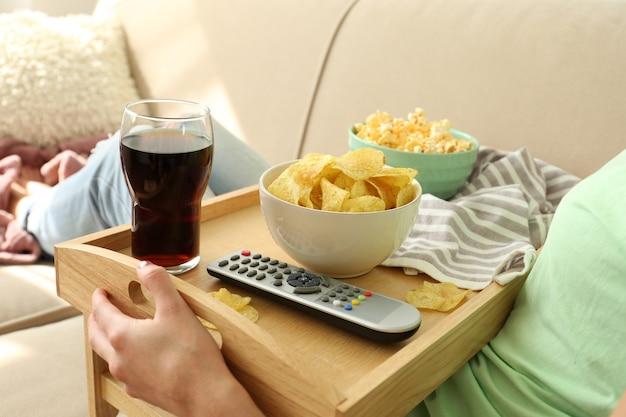 Девушка с подносом обедает на диване