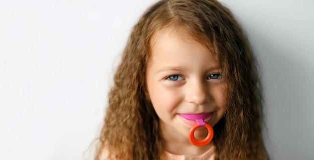 歯の噛み合わせを矯正するための前庭ハードマウスガードプレートを持つ少女