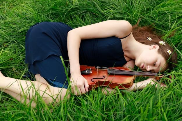 Девушка со скрипкой лежит на траве. азиатская внешность. фото высокого качества