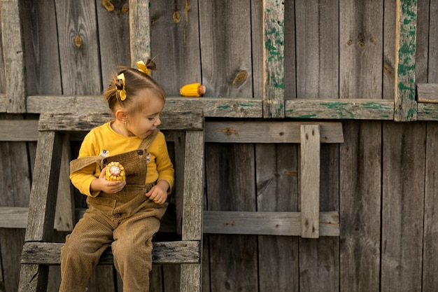 とうもろこしの穂を手にした少女が古い階段に座っている