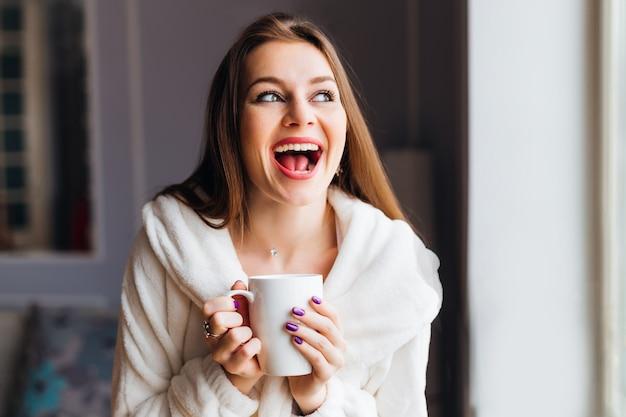 お茶やコーヒーを抱えて感情的な笑顔の女の子。