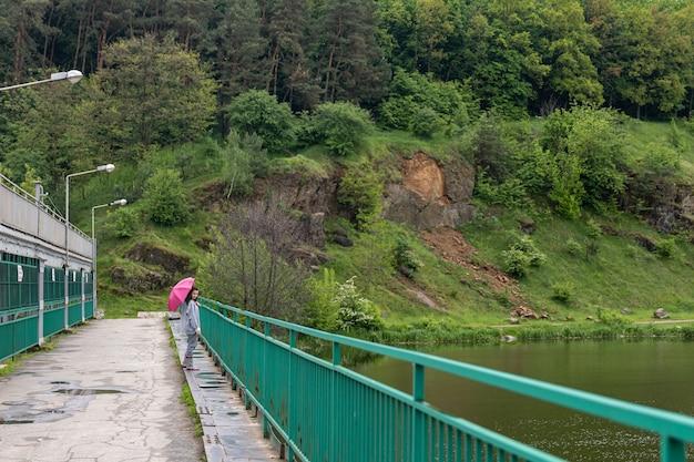 曇りの日に傘をさして森を散歩する女の子が橋の上に立つ
