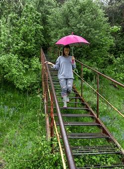 우산을 든 소녀가 비오는 날씨에 숲을 산책합니다.