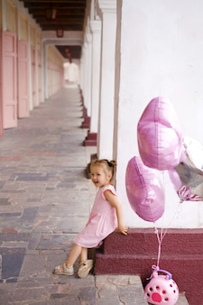 風船と動物を運ぶおもちゃのバスケットを持つ少女は、都市の建物の列に立っています