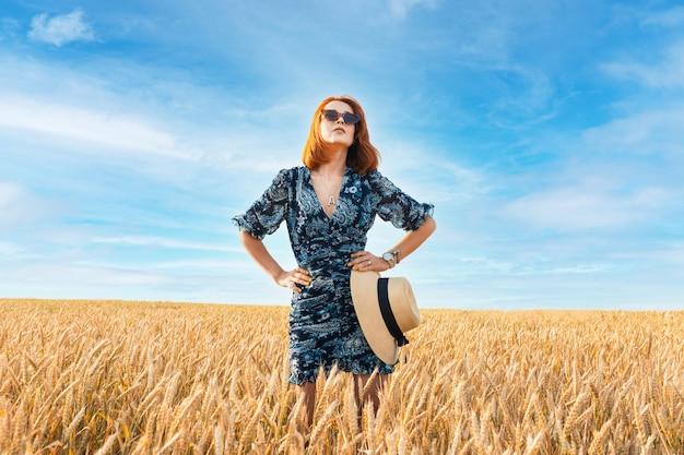 밀밭 한가운데 서 있는 아름다운 머리를 가진 소녀. 건강한 자연 모발
