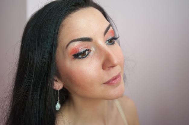 아름답게 칠한 속눈썹과 눈꺼풀을 가진 소녀. 메이크업 아티스트는 배경에 검은 속눈썹 마스카라 클로즈업으로 소녀를 그립니다. 아름다운 갈색 머리. 화려한 눈꺼풀