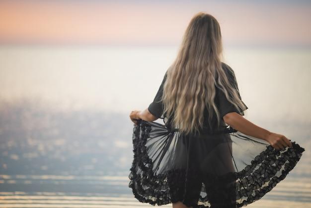 Девушка со светлыми шикарными волосами в черном купальнике и кружевном платке гуляет по лиману.