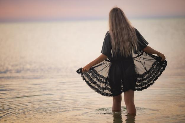 검은 비키니와 레이스 숄을 입은 세련된 금발 머리를 한 소녀가 강어귀를 따라 걷는다