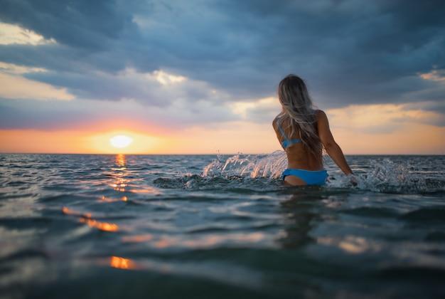 파란색 수영복에 금발 머리를 한 소녀가 일몰 배경의 강어귀에 앉아 있는 동안 옆으로 튀었다