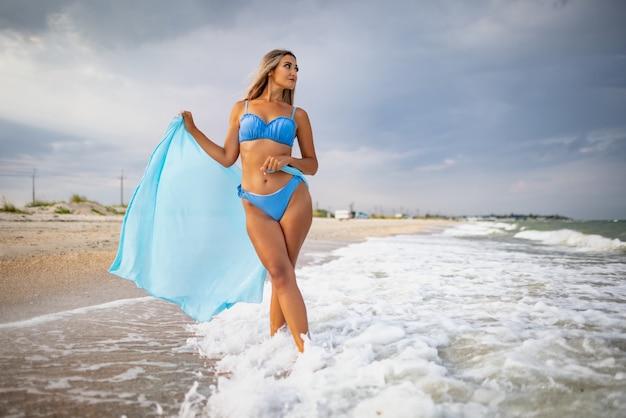 Девушка со светлыми волосами в голубоватом купальнике и яркой шали гуляет по пляжу