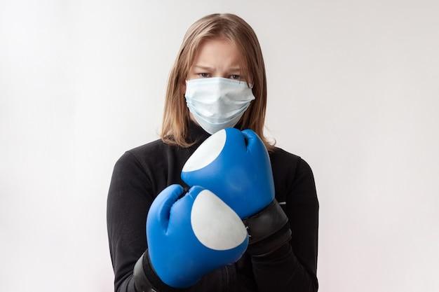 의료용 마스크와 파란색 권투 장갑을 낀 금발 머리를 한 소녀가 권투 선수의 포즈를 취하고 있으며, 오른손은 얼굴 근처의 왼쪽 앞에 있습니다.
