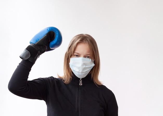 의료 마스크와 파란색 권투 장갑에 금발 머리를 가진 소녀