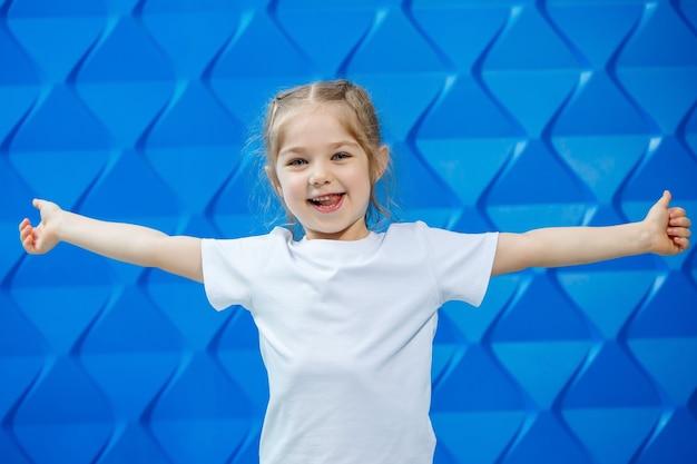 파란색 배경에 흰색 티셔츠를 입은 금발의 소녀. 그녀는 웃으며 손을 흔든다