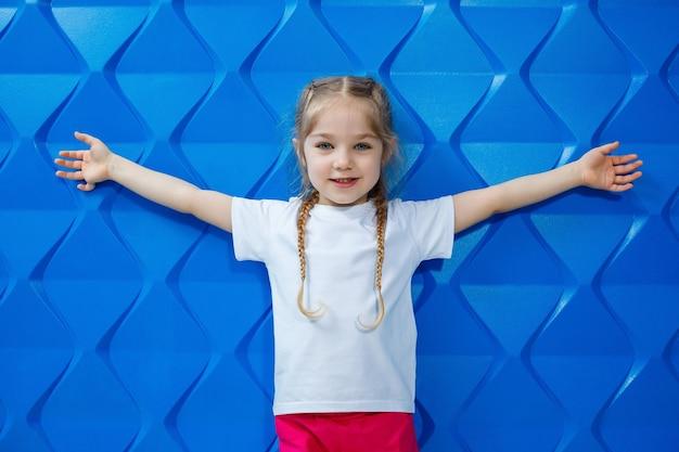 Девушка со светлыми волосами в белой футболке на синем фоне. она улыбается и машет руками