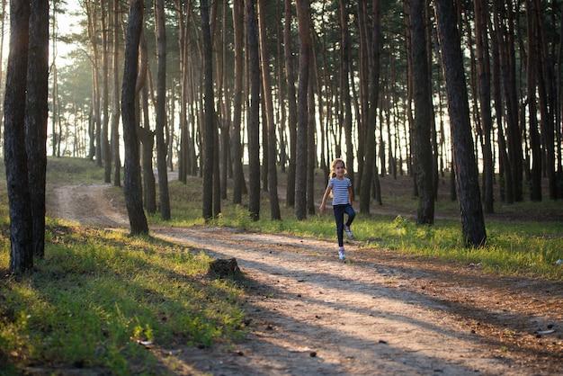 금발 머리 소녀는 아침에 모든 가지를 뛰어 넘는 숲길을 따라 달린다