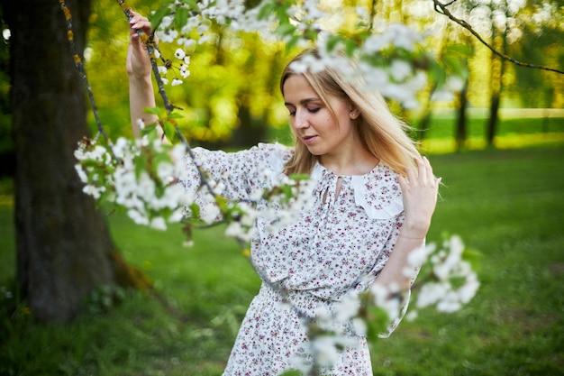Девушка со светлыми волосами в цветочном платье стоит рядом с цветущим деревом