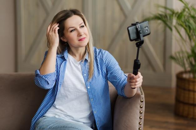 シャツを着たブロンドの髪の少女が電話の画面を見て自分撮りをします
