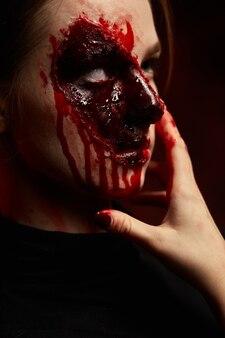 보라색 배경에 할로윈을 위해 얼굴에 피 묻은 화장을 한 소녀