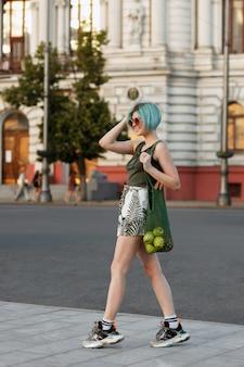 青い髪の少女が緑の果物の袋を持って街を歩きます。明るい夏