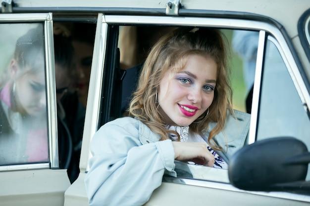 밝은 화장을 한 소녀가 복고차 창밖을 내다본다.