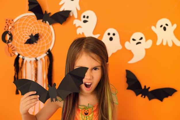 紙のバットで片目を覆って怒って怒って立っている巻き毛の女の子