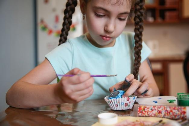 어두운 긴 머리띠를 가진 소녀가 집에서 테이블에 앉아 부활절 달걀을 장식합니다.