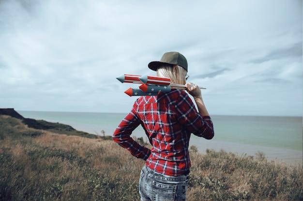 Девушка с фейерверком в руках готовится к запуску ракеты в честь празднования дня независимости 4 июля