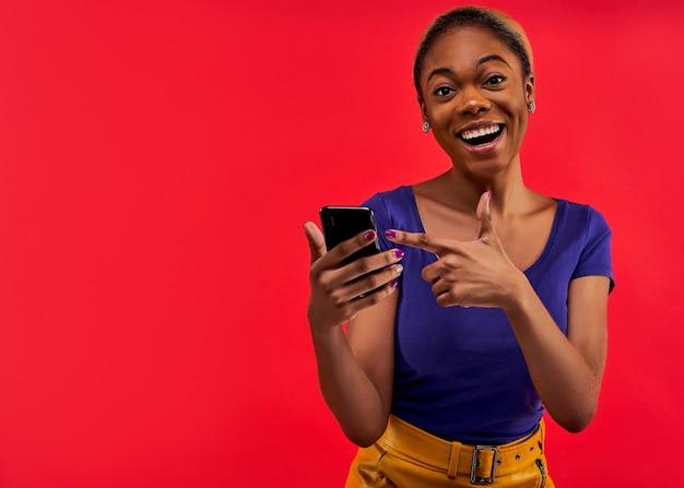 Девушка с прической в синей футболке и желтой юбке показывает на смартфон в руке