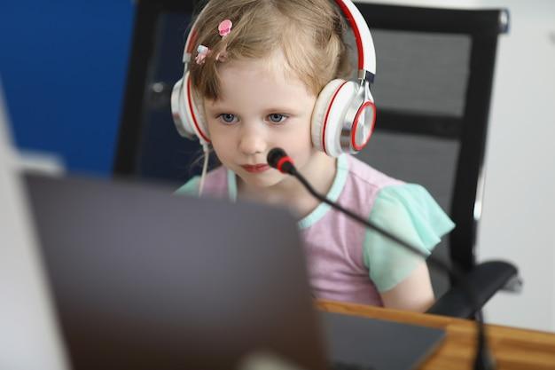 ヘッドフォンを持った女の子がノートパソコンの画面をのぞき込みます。子供のためのオンライン教育。パンデミックおよび検疫中の教育