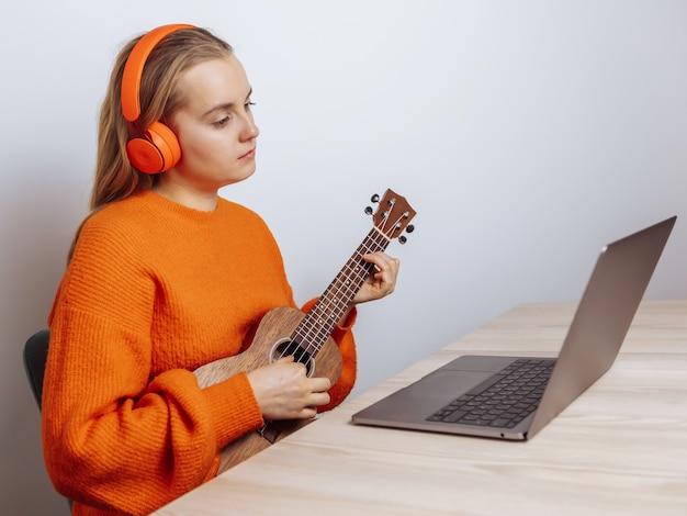 Девушка в наушниках играет на гавайской гитаре на своем ноутбуке