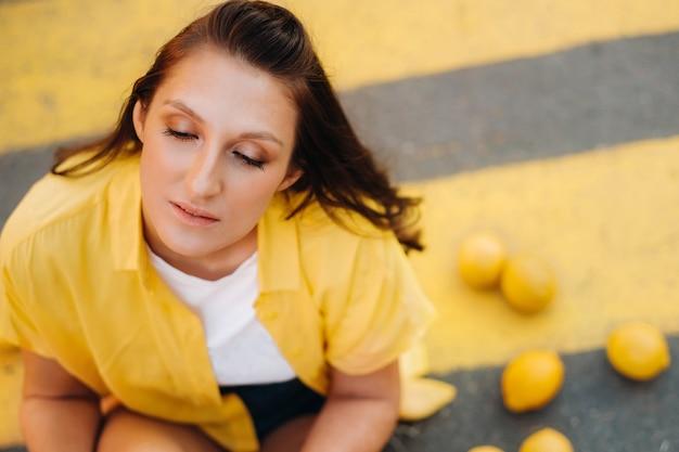黄色いシャツ、ショートパンツ、黒い靴を履いたレモンの女の子が、街の黄色い横断歩道に座っています。レモンムード。