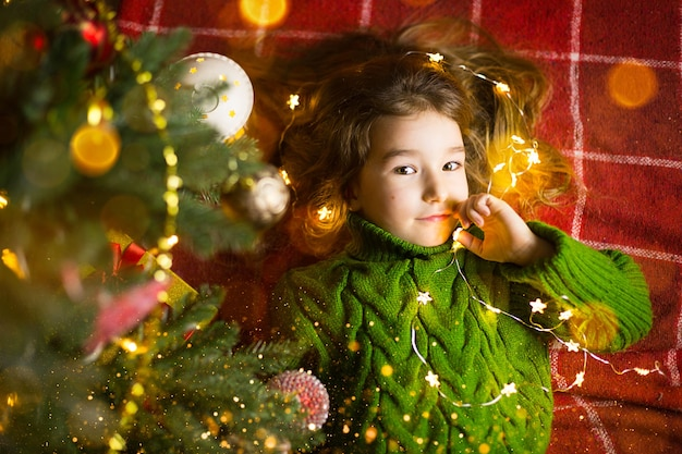 長い髪と花輪を持つ少女は、暖かいニットのセーターのおもちゃでクリスマスツリーの下の赤い格子縞の上に横たわっています。クリスマス、お正月、子どもたちの感情、喜び、奇跡への期待、そして贈り物