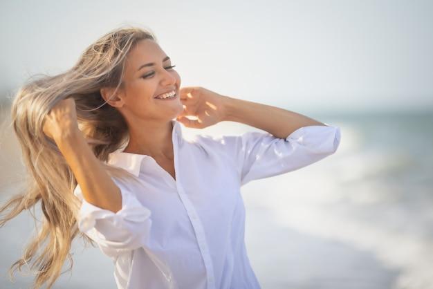 푸른빛이 도는 수영복과 셔츠를 입은 긴 머리를 한 소녀가 해변에서 머리카락을 훑고 지나간다